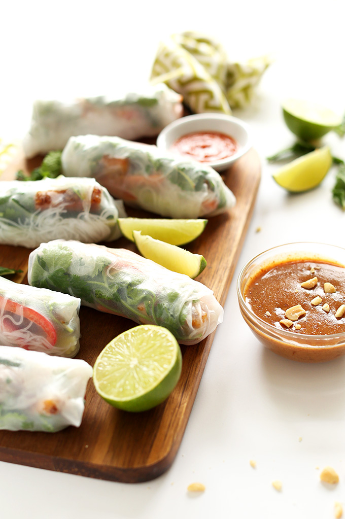 Batch of our homemade Vegan Spring Rolls on a cutting board with fresh limes and dipping sauce