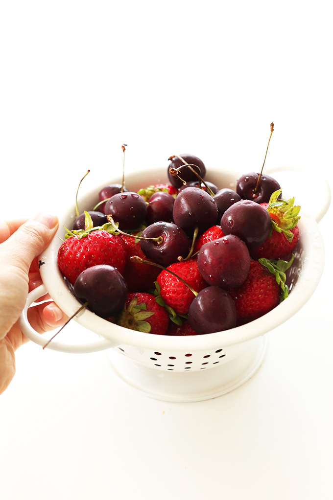 Mini colander filled with cherries and strawberries for making homemade Fresh Fruit Compote