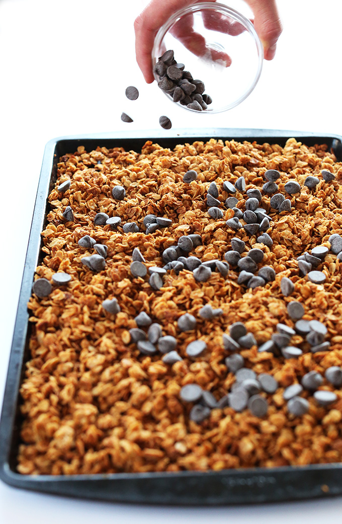 Sprinkling chocolate chips onto a baking sheet filled with Gluten-Free Peanut Butter Granola