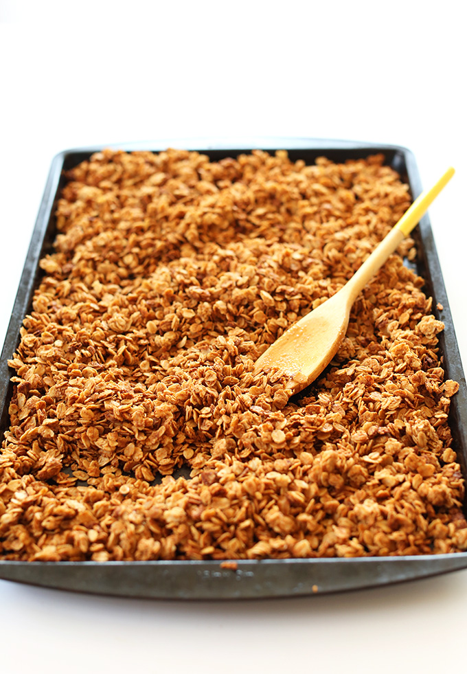Wooden spoon resting on a baking sheet filled with Peanut Butter Chocolate Chip Granola