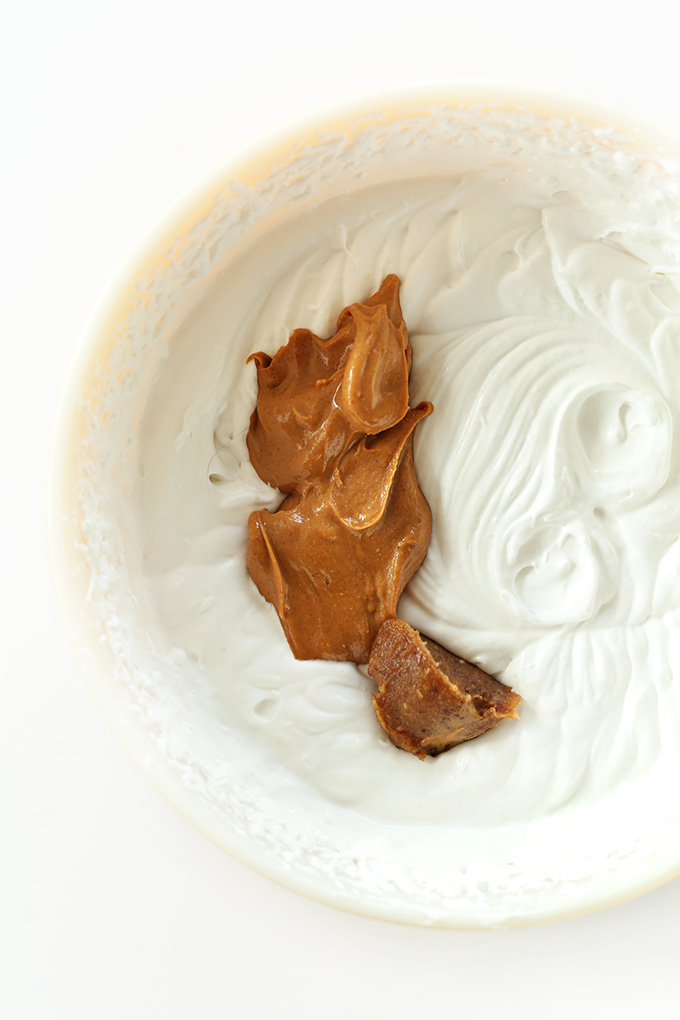 Dollop of peanut butter in a bowl of coconut whipped cream