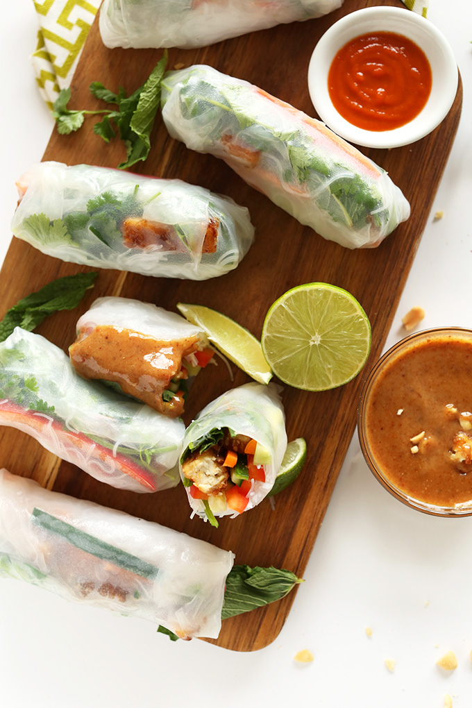 Wood cutting board filled with Vietnamese Spring Rolls and dipping sauce for a delicious vegan snack