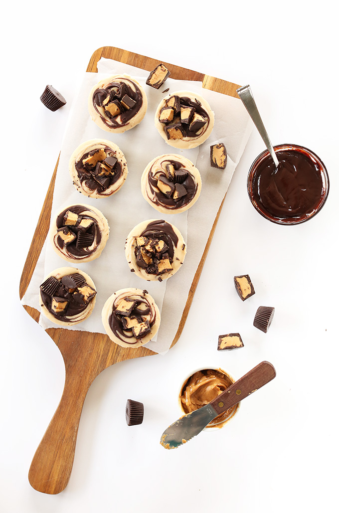Homemade Vegan Peanut Butter Cup Cheesecakes on a parchment-lined cutting board