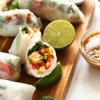 Sliced open Tofu Vietnamese Spring Roll on a cutting board with limes and more rolls