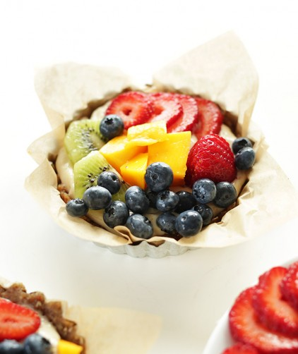 One of our No Bake Lemon Cookie Fruit Tarts in a parchment-lined mini tart pan