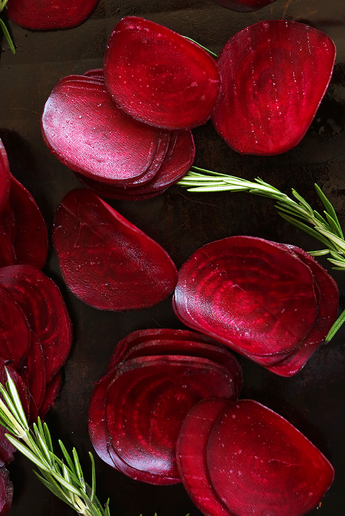 Thinly sliced vibrant red beets with rosemary on a baking sheet