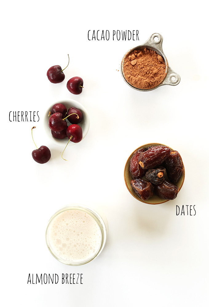 Fresh cherries, cacao powder, dates, and almond milk for making Chocolate Cherry Almond Milk