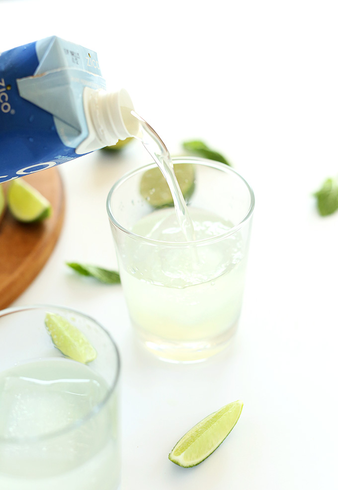Pouring coconut water into glasses for Coconut Gin and Tonics