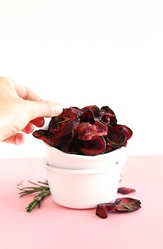 Grabbing a Baked Rosemary Beet Chip for a delicious vegan snack