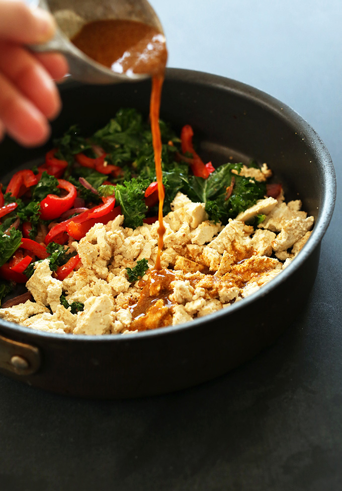 Pouring spice mix over skillet for our Easy Tofu Scramble recipe