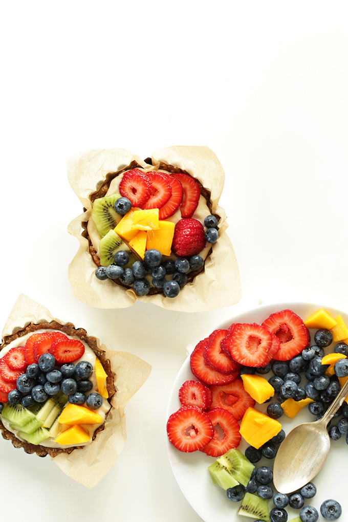 7-ingredient Lemon Cookie Fruit Tarts and a plate of fresh fruit in a rainbow of colors
