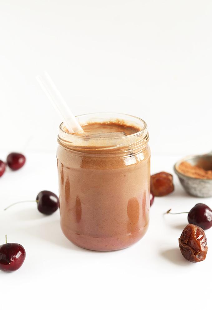 Glass jar of Chocolate Cherry Almond Milk with a straw