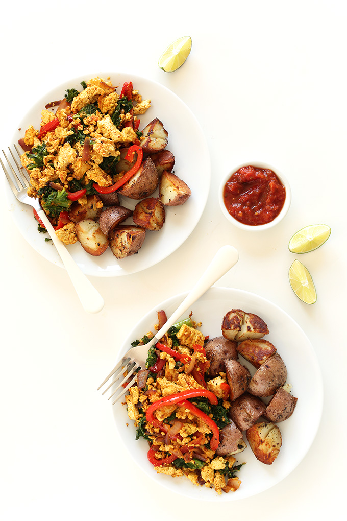 Two plates of our simple Veggie Tofu Scramble with breakfast potatoes, limes, and ketchup