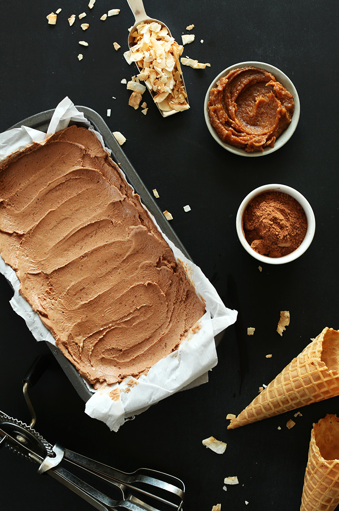 Pan of super creamy No-Churn Vegan Chocolate Ice Cream surrounded by date caramel and other ingredients