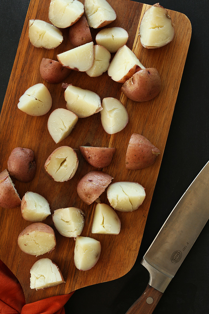 Partially cooked chopped red potatoes on a wood cutting board