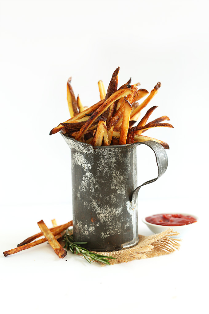 Tin container filled with simple vegan matchstick fries and a bowl of homemade ketchup