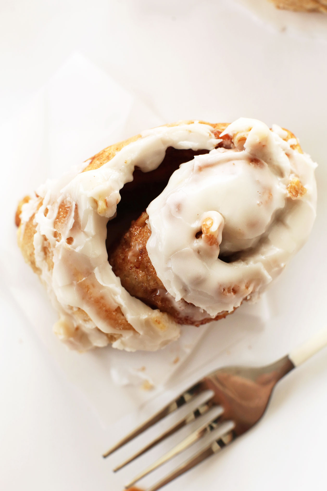 Partially unrolled gooey Banana Bread Cinnamon Roll with icing