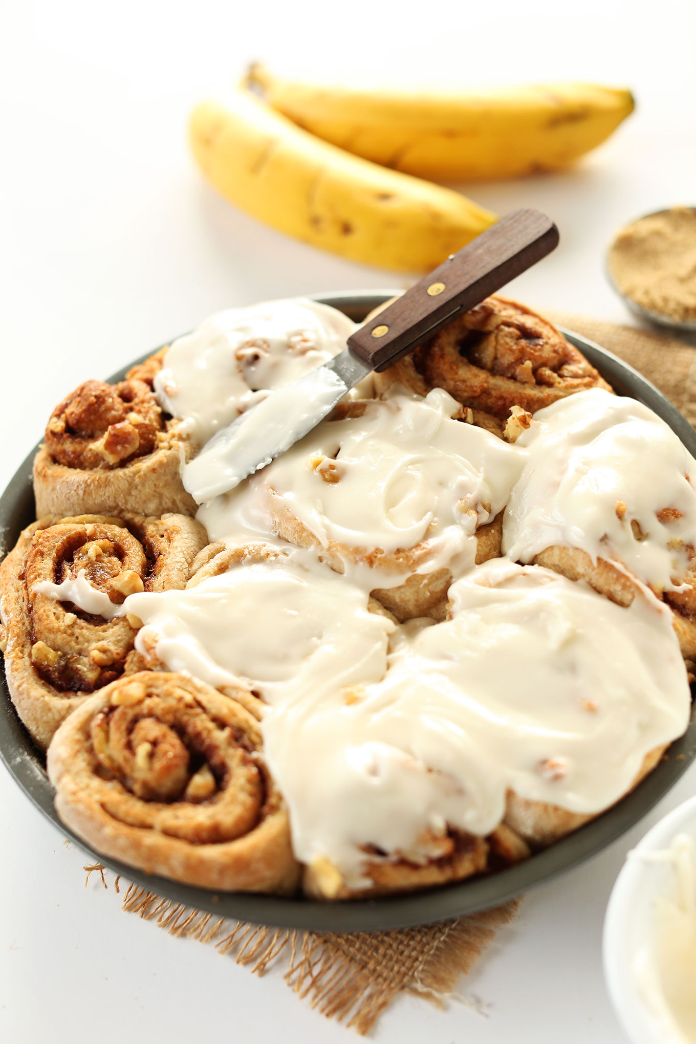 Spreading icing over a batch of freshly baked Vegan Banana Bread Cinnamon Rolls
