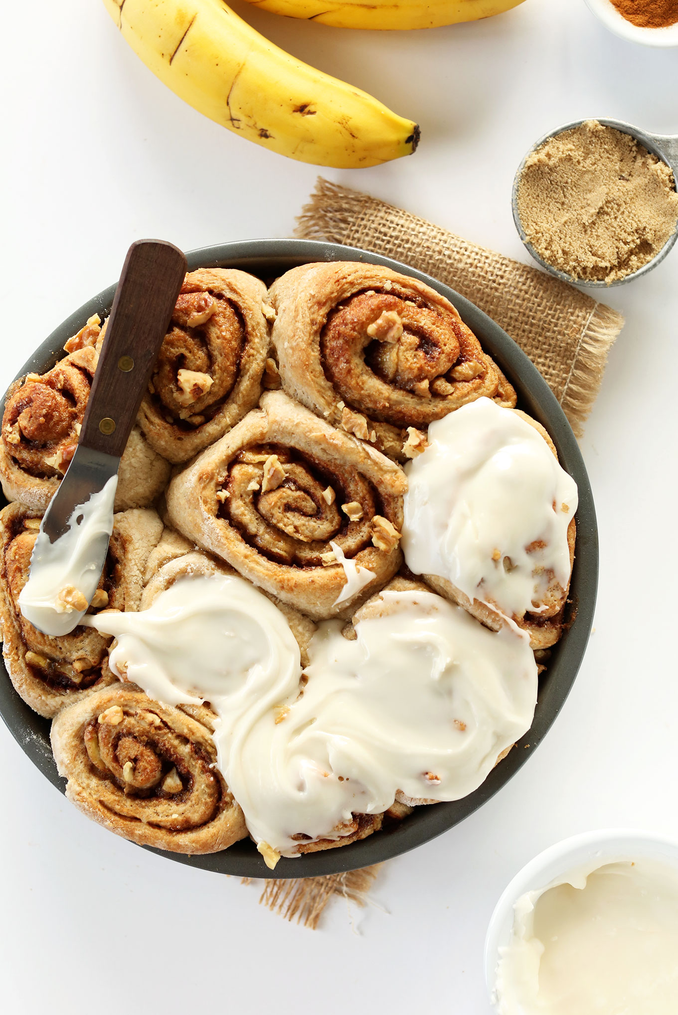 Spreading icing over freshly baked Vegan Banana Bread Cinnamon Rolls