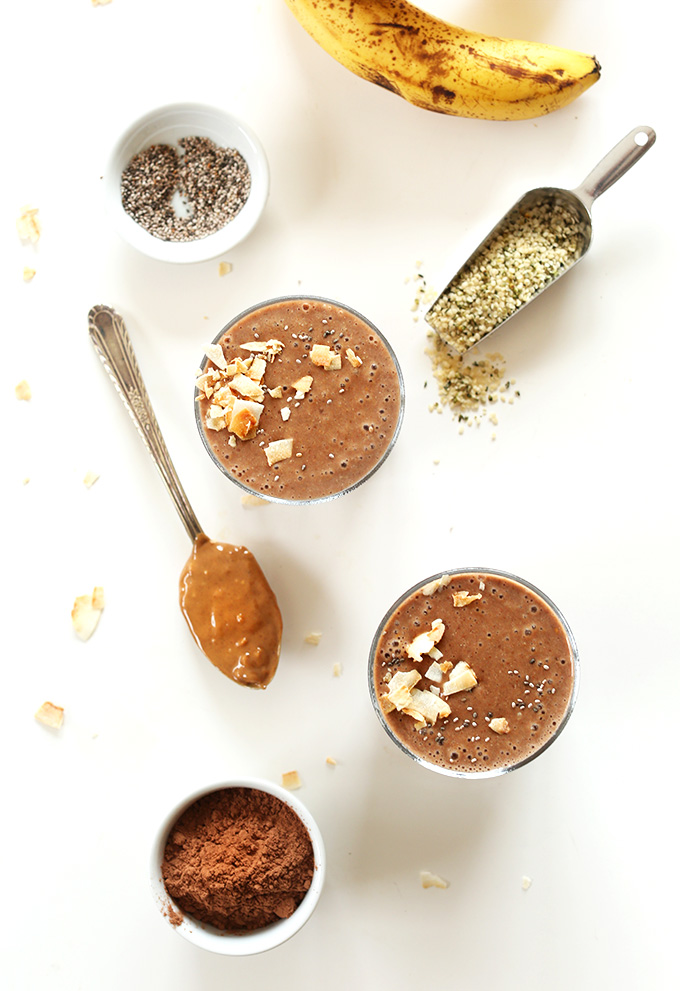 Two homemade recovery drinks surrounded by hemp seeds, chia seeds, banana and a spoonful peanut butter