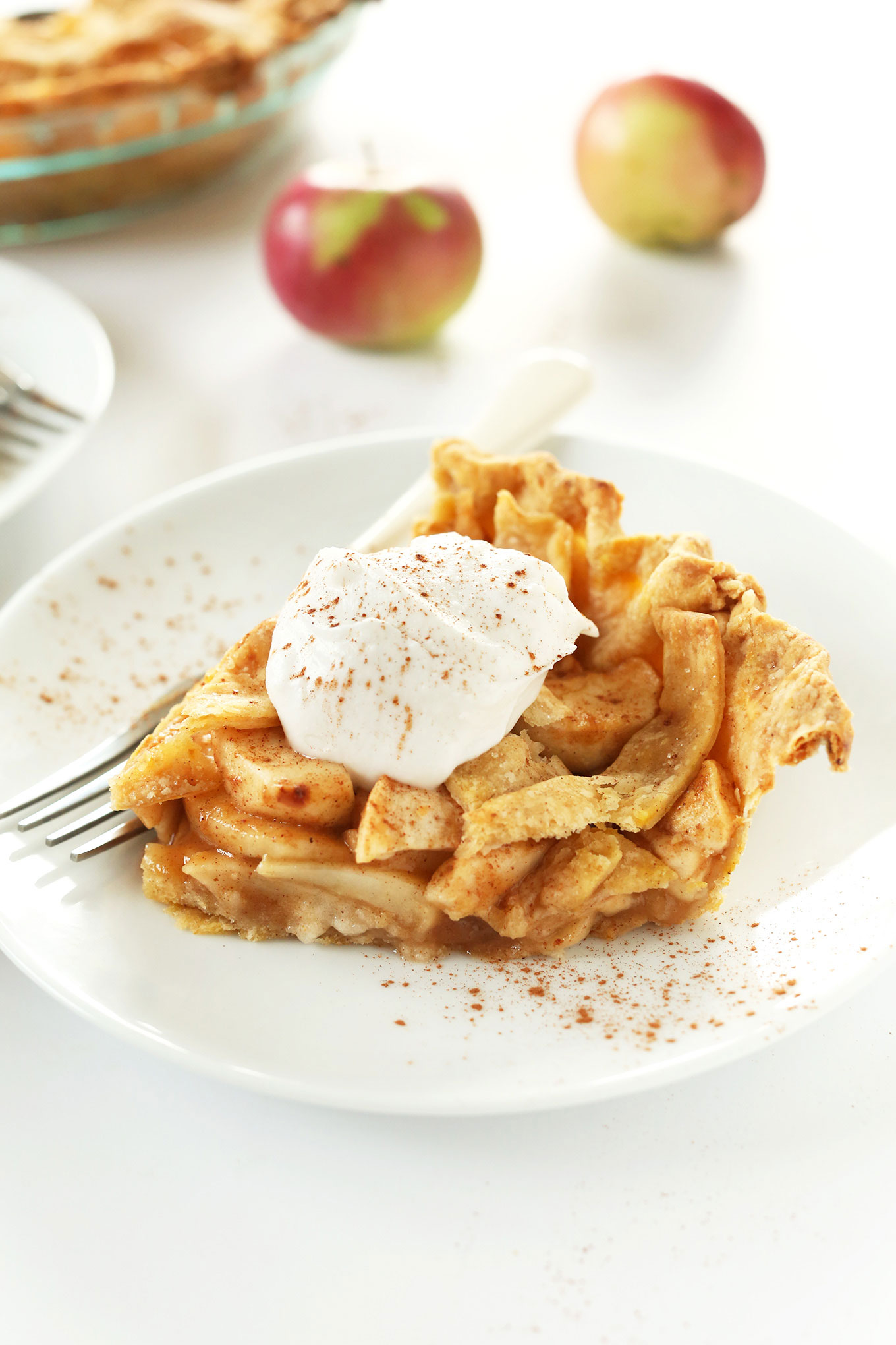 Side view of a slice of apple pie topped with coconut whip