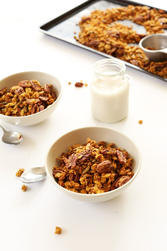 Serving bowls and baking sheet filled with Pumpkin Pecan Granola alongside a glass of nut milk