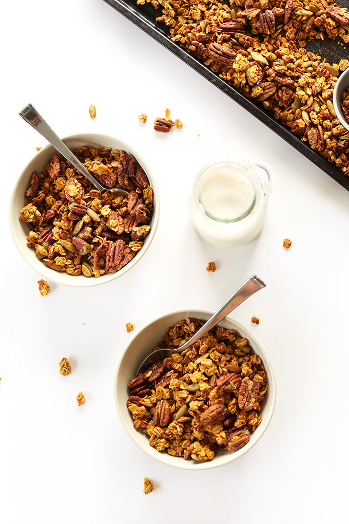 Bowls of Pumpkin Pecan Granola and a jug of nut milk for a delicious gluten-free vegan breakfast