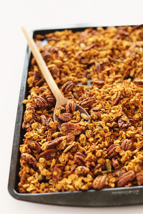 Using a wooden spoon to stir a tray of Pumpkin Pecan Granola