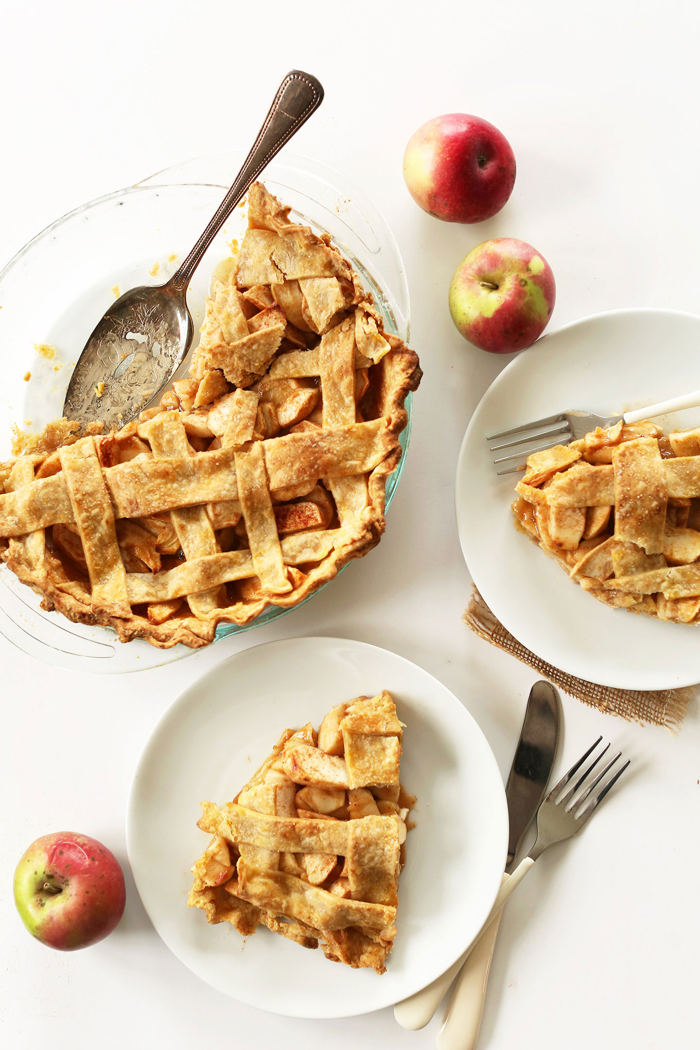 Plates with slices of vegan apple pie alongside the rest of the pie