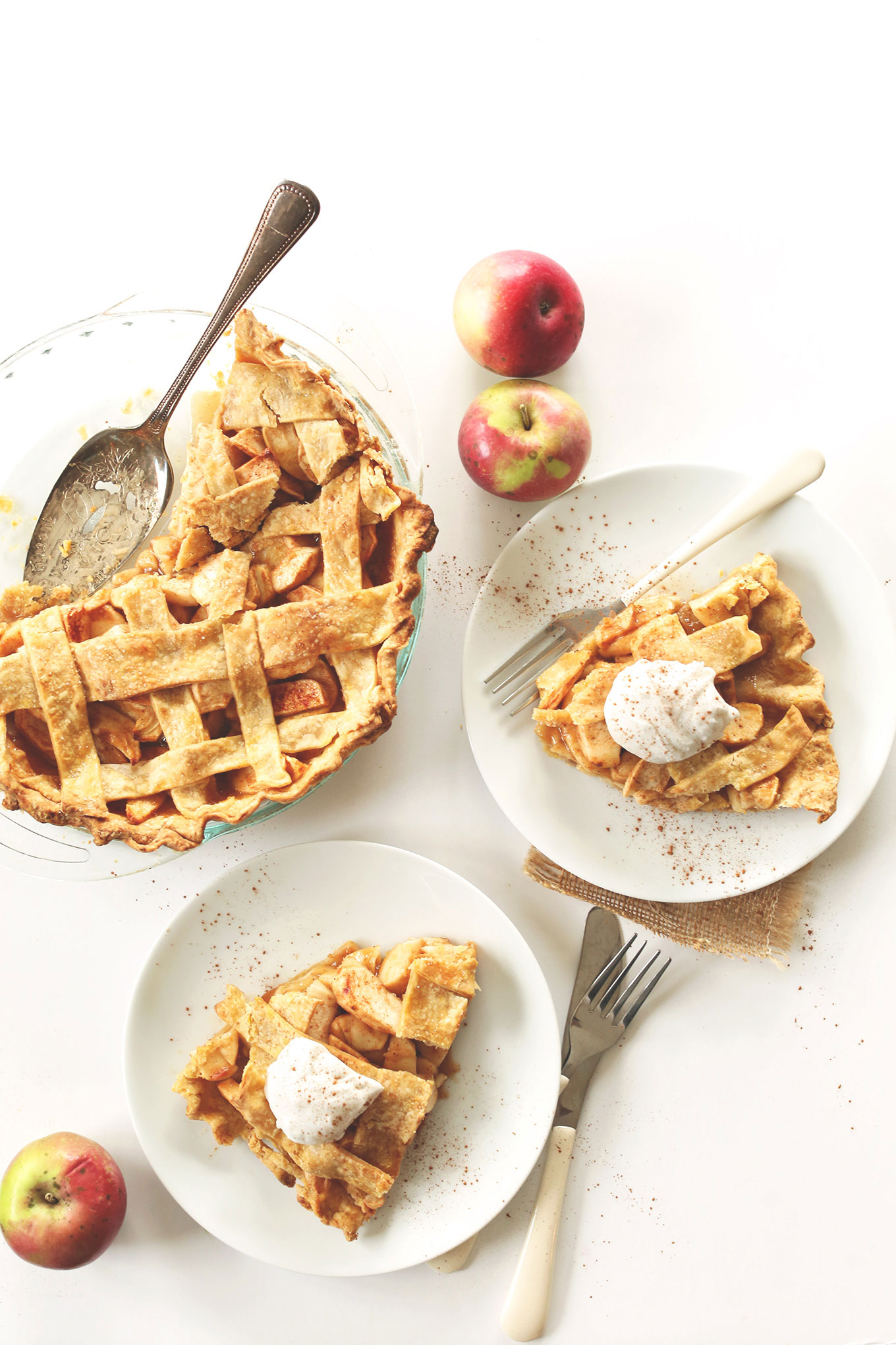 Slices of vegan apple pie with coconut whipped cream resting alongside the rest of the pie