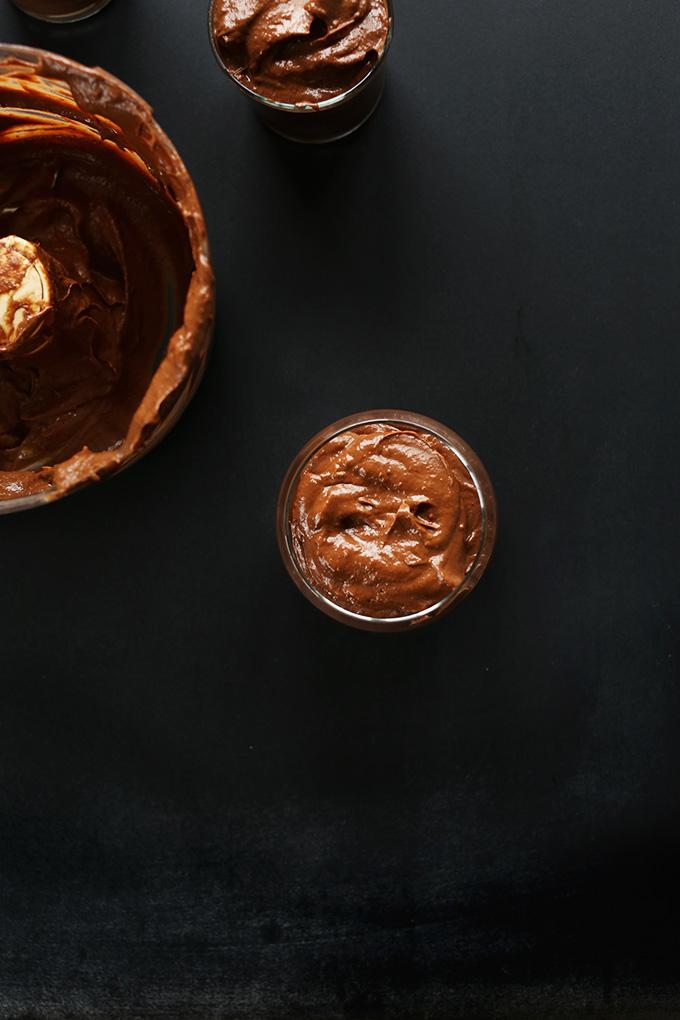 Food processor and glass jars of vegan Chocolate PB Avocado Pudding