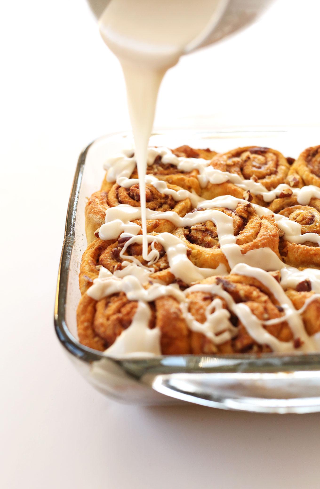 Pouring glaze onto a pan of Vegan Pumpkin Cinnamon Rolls