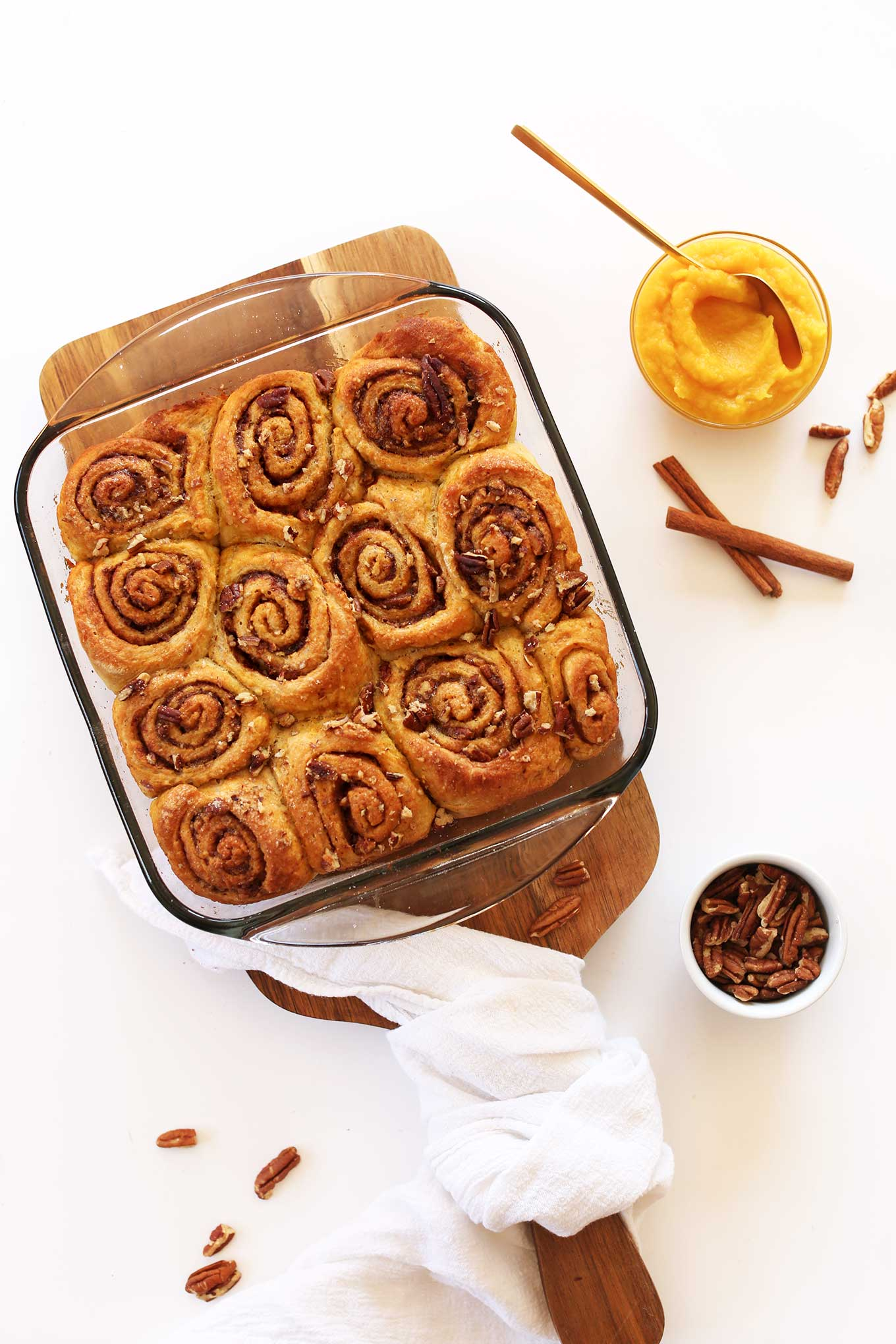 Pan of freshly baked Vegan Pumpkin Cinnamon Rolls alongside cinnamon sticks and bowls of pecans and pumpkin puree