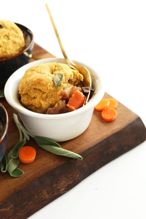 Wood cutting board featuring bowls of our Vegan Fall Pot Pies loaded with veggies