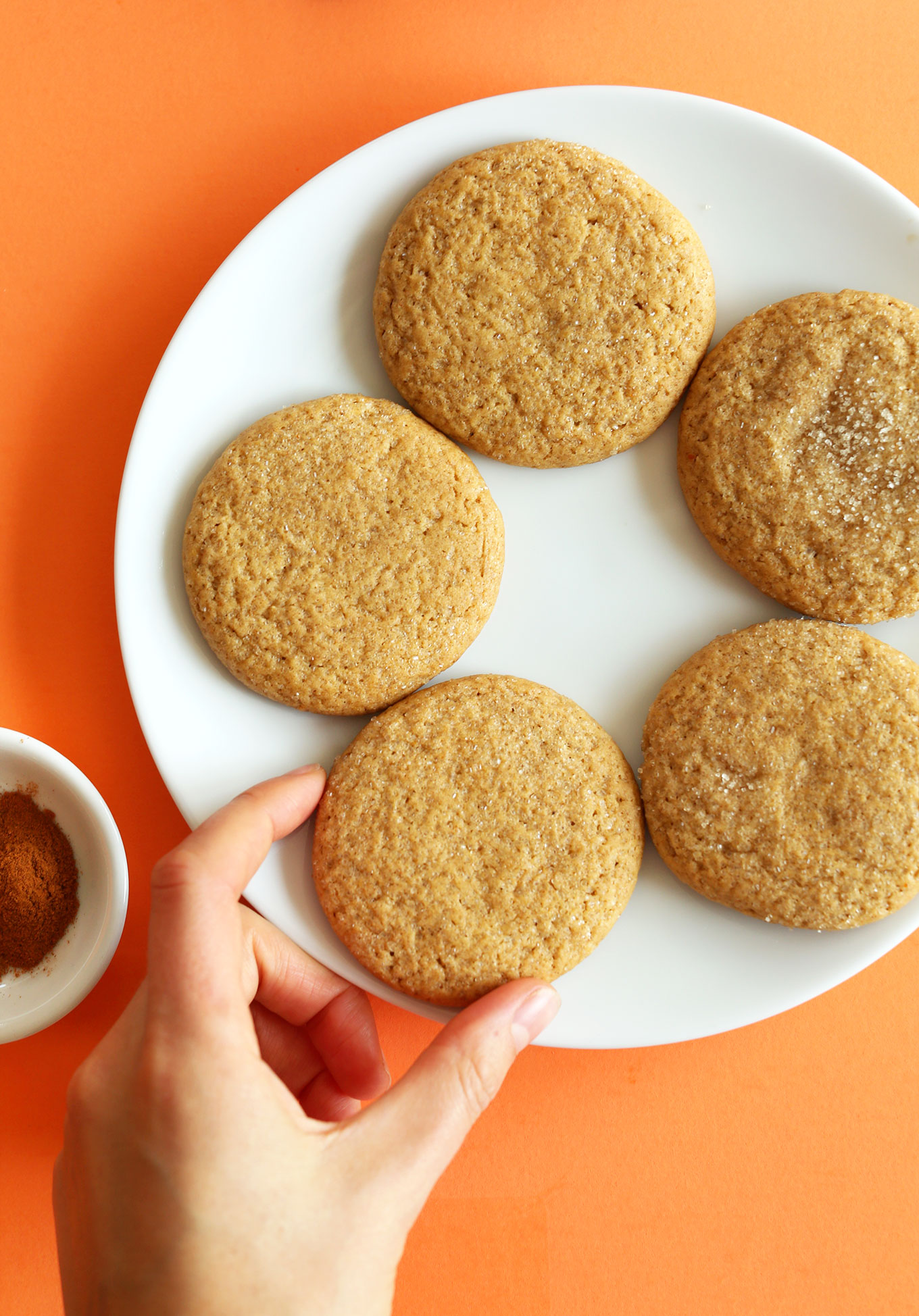 Grabbing a Vegan Pumpkin Sugar Cookie from a plate