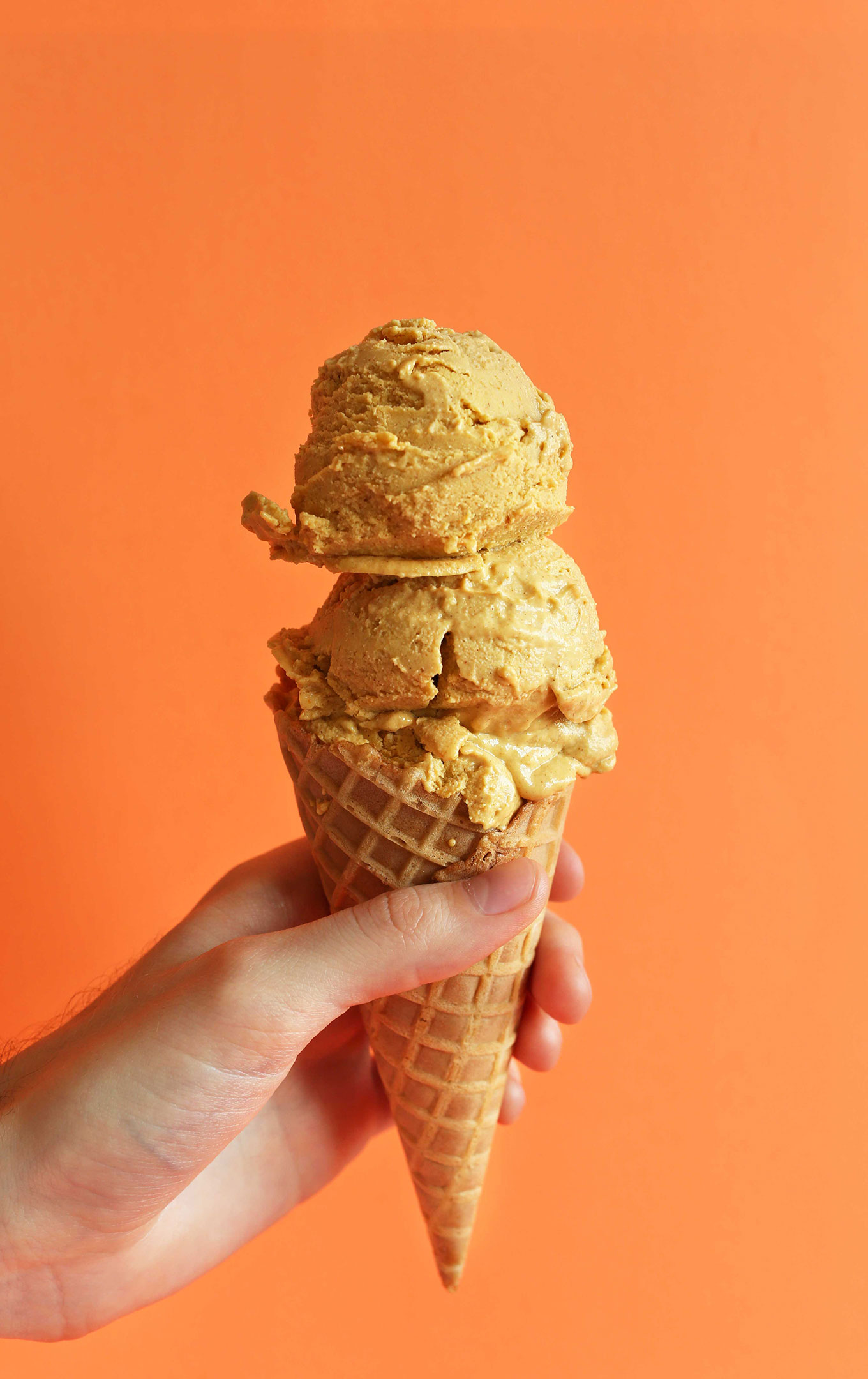 Holding up a cone with scoops of Creamy Pumpkin Pie Ice Cream