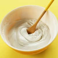Wooden spoon in a bowl of homemade Coconut Whipped Cream