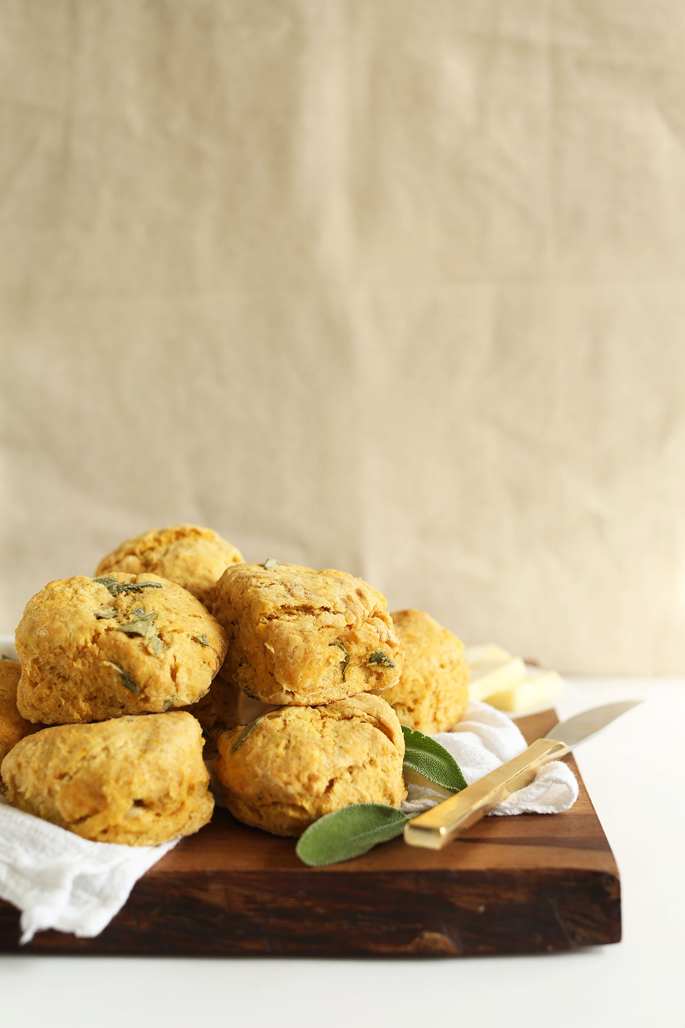 Stack of fluffy vegan Pumpkin Sage Biscuits resting on a cutting board
