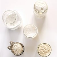 Jars and measuring cups of gluten free flours for making a homemade Gluten Free All Purpose Flour Blend