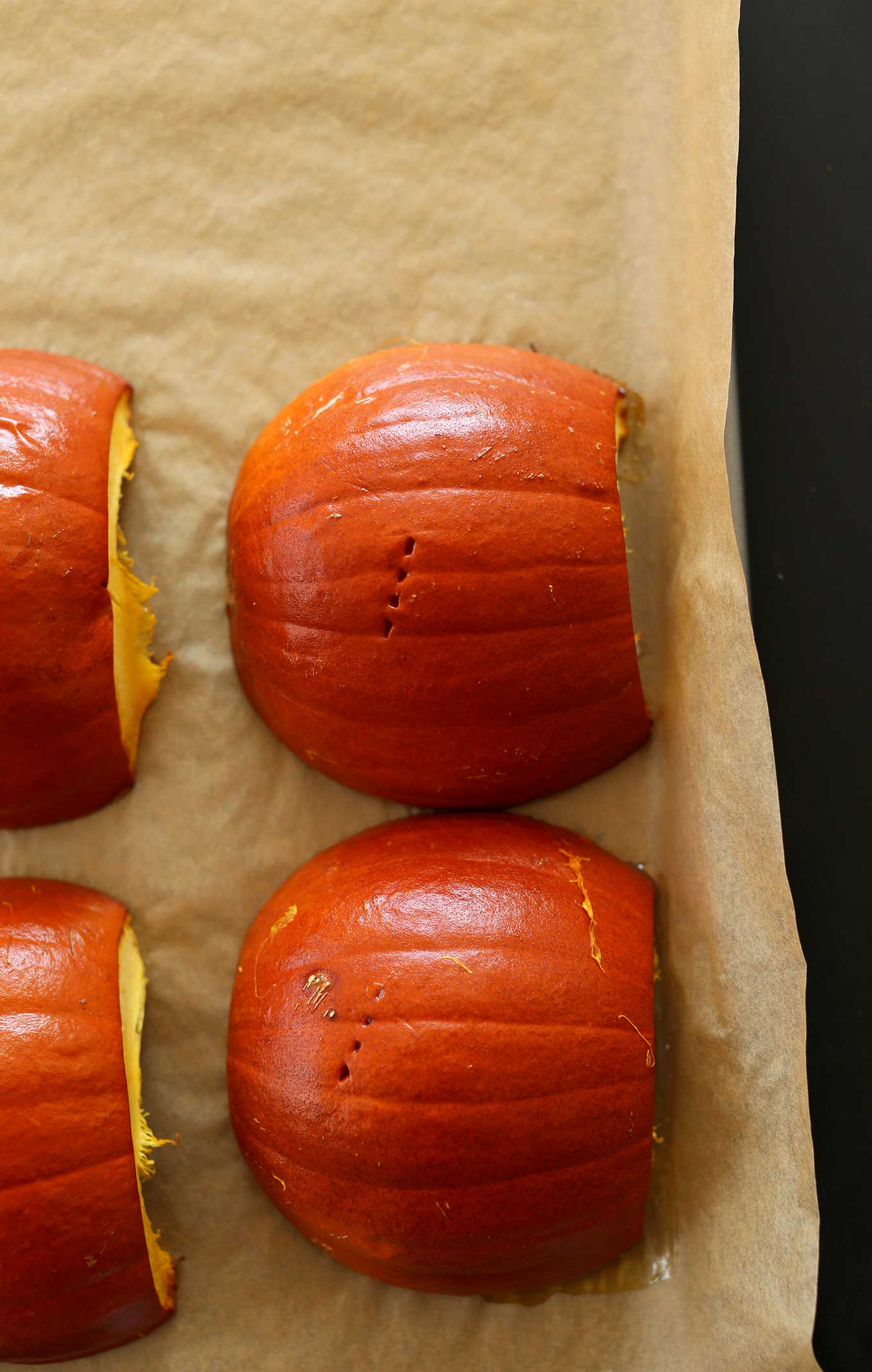 Freshly roasted sugar pumpkins on a parchment-lined baking sheet
