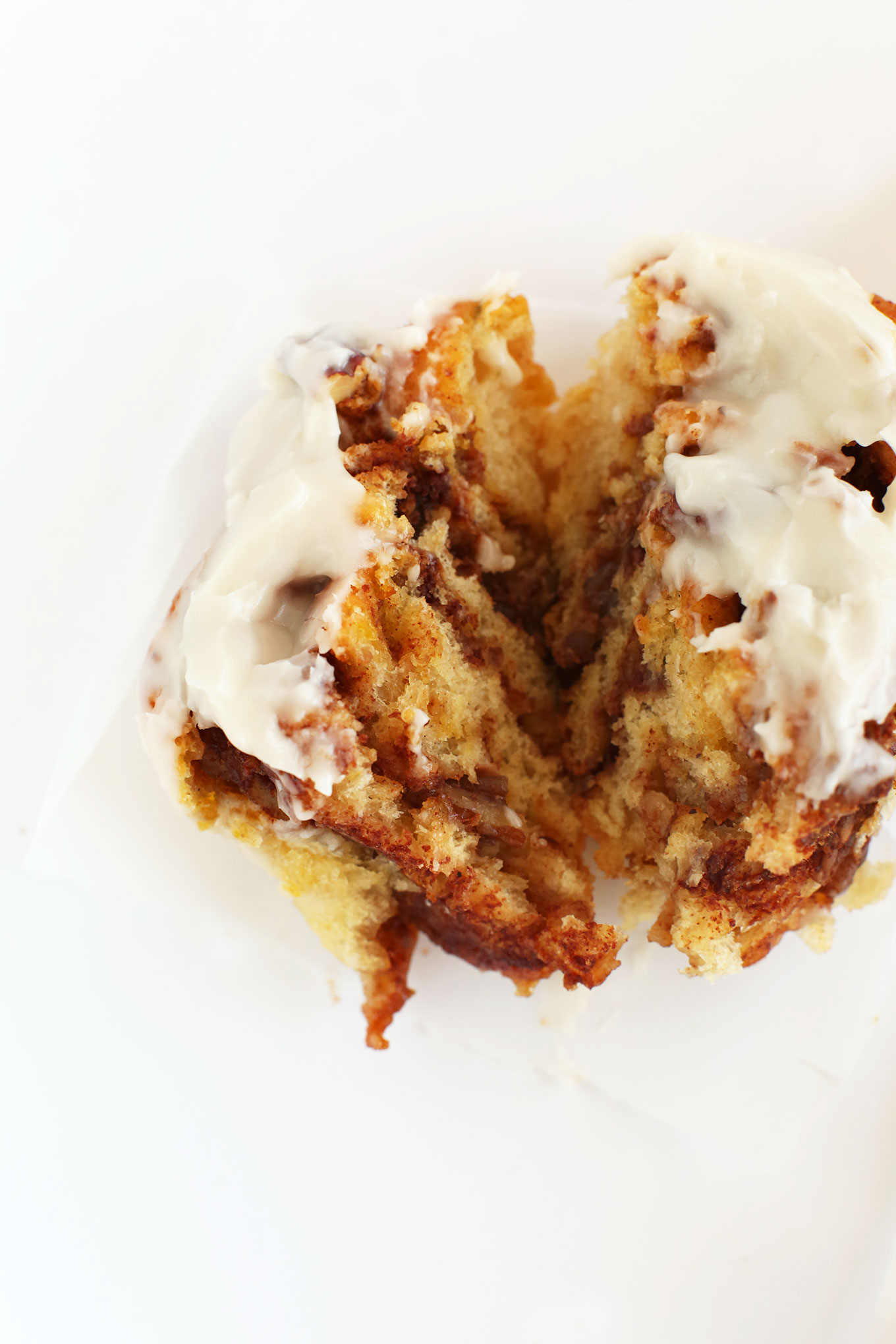 Cut open gooey Pumpkin Cinnamon Roll with icing