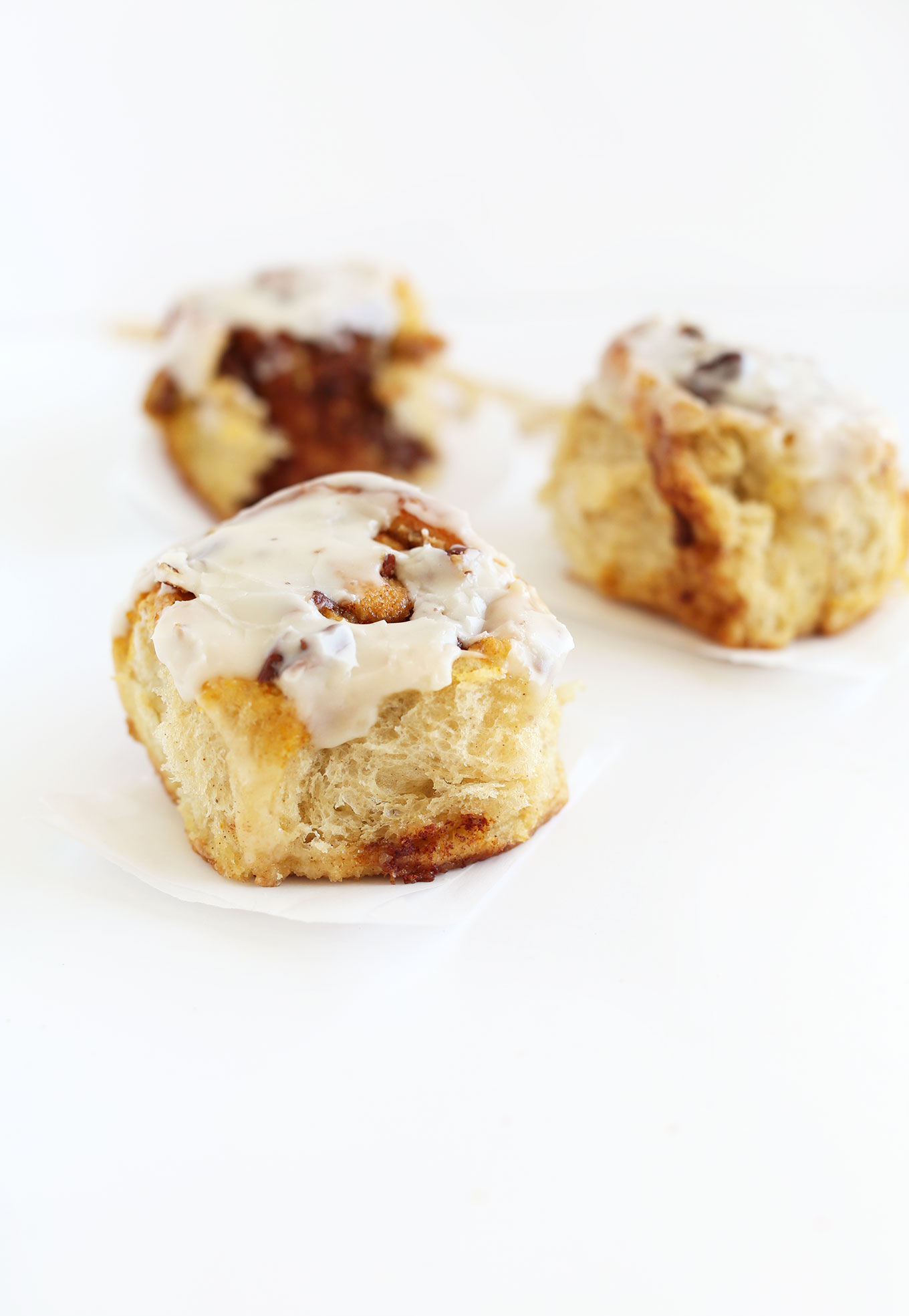 Freshly iced Pumpkin Cinnamon Rolls on squares of parchment paper