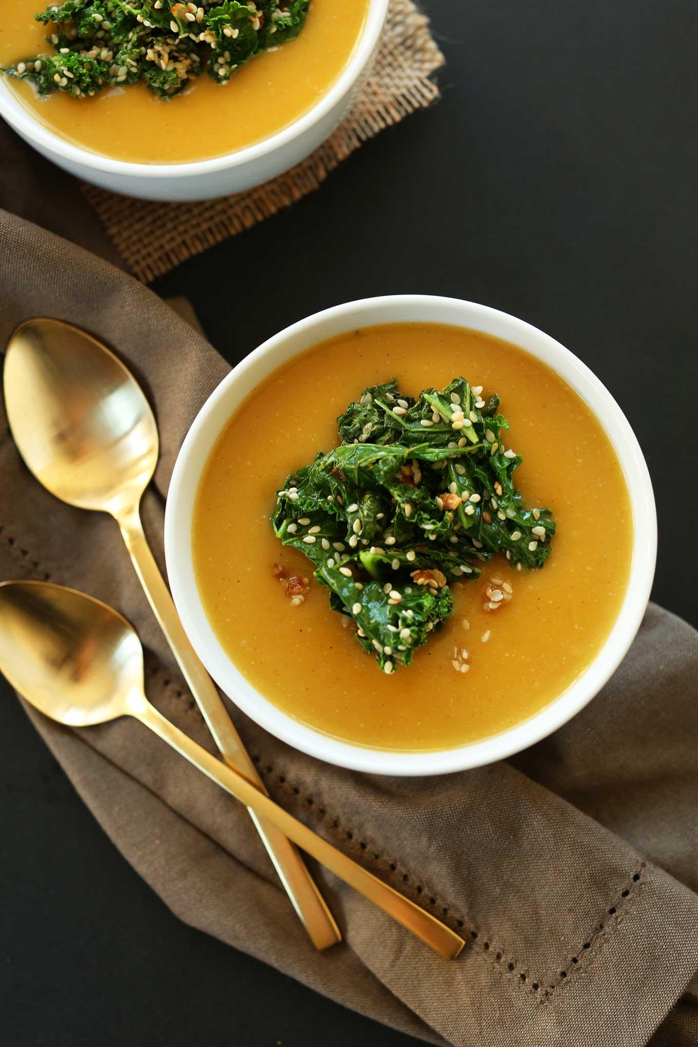 Overhead shot of bowls of gluten-free vegan pumpkin soup with sesame kale topping