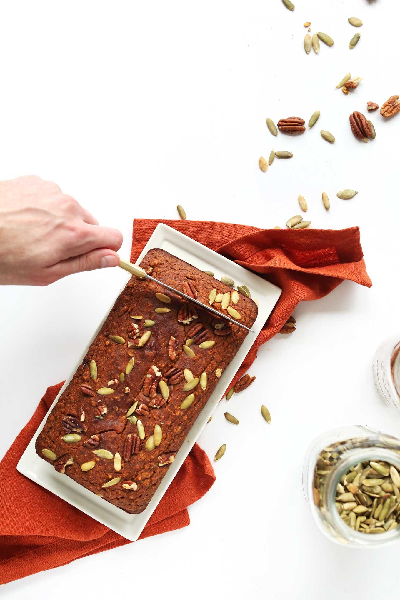 Slicing into a loaf of Vegan Gluten-Free Pumpkin Bread
