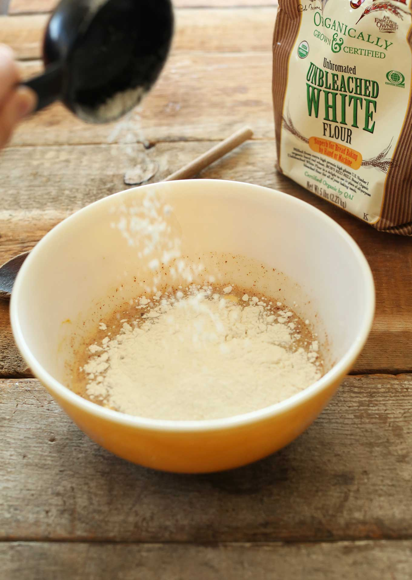 Pouring flour into the dough for making our Vegan Pumpkin Cinnamon Rolls recipe