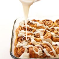 Drizzling icing onto a batch of delicious Vegan Pumpkin Cinnamon Rolls