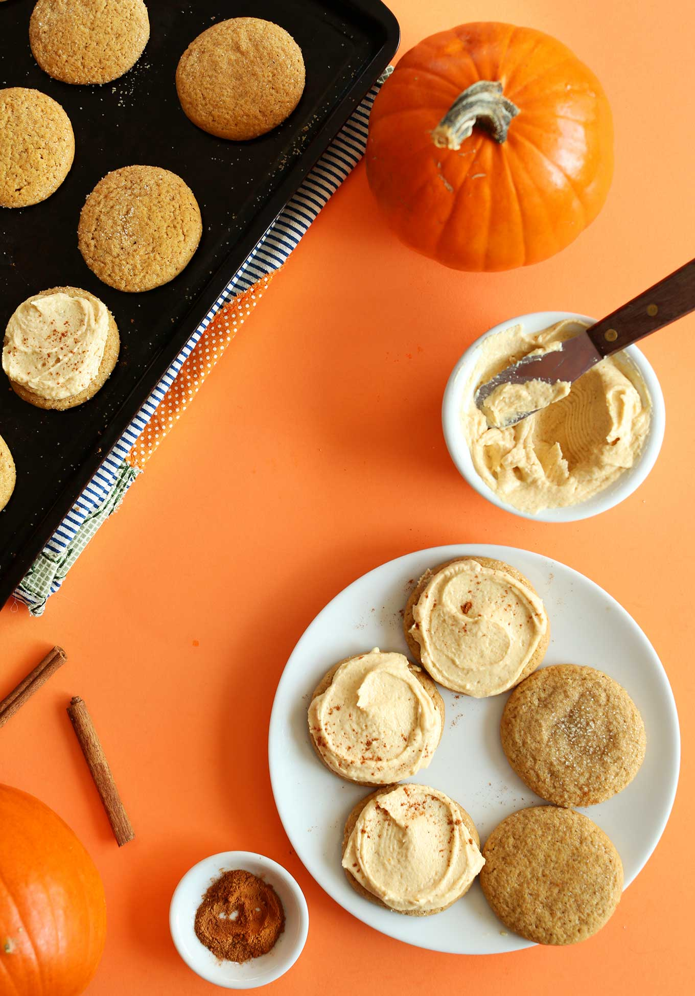 Plate and baking sheet with a partially-frosted batch of homemade Vegan Pumpkin Sugar Cookies