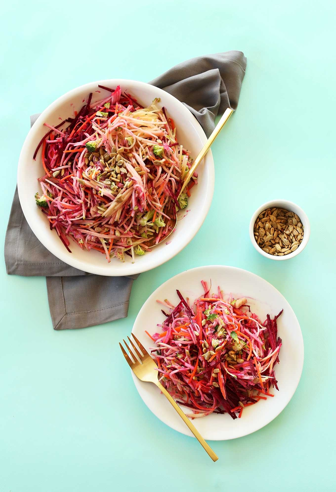 Plate and big bowl of colorful fall slaw with a tangy vegan dressing