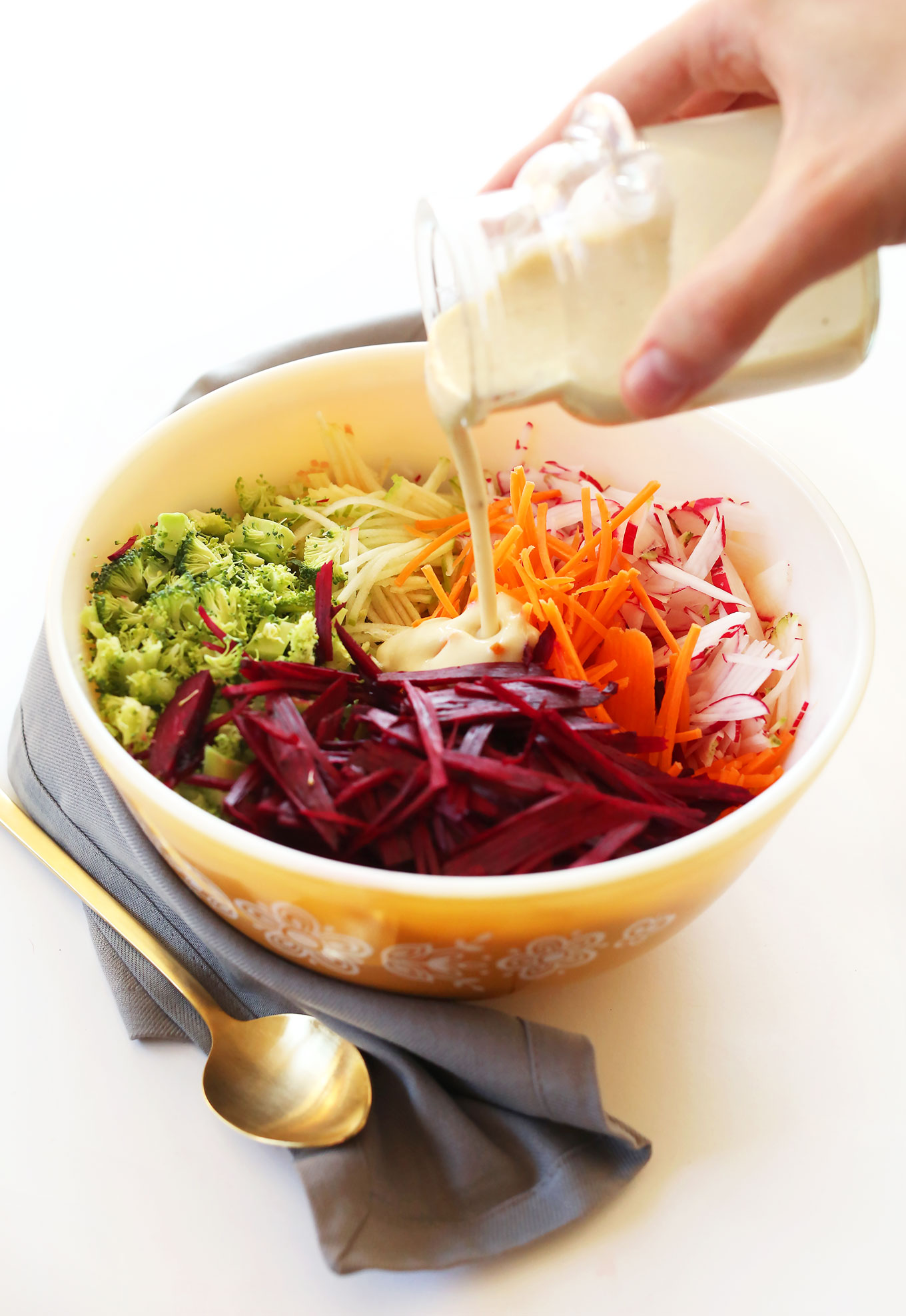 Pouring creamy vegan dressing onto our fall slaw