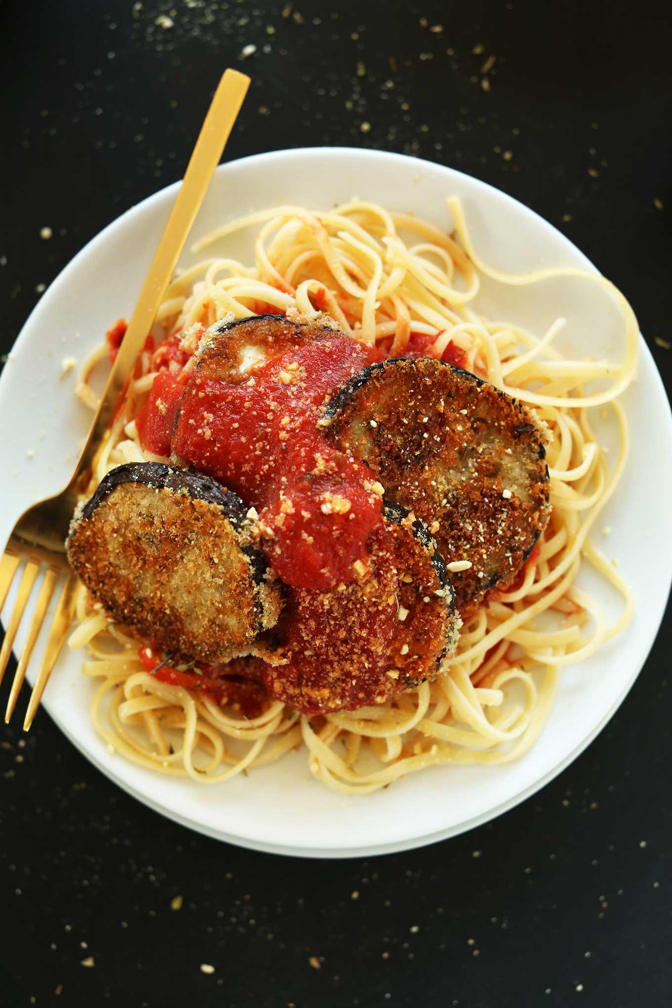 Big bowl of linguine noodle topped with marinara and vegan eggplant parmesan